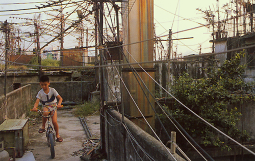 Children ride bikes on rooftop of Kowloon Walled City