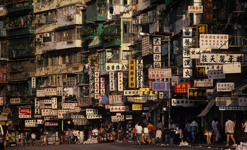 Colorful signs line street in front of Kowloon Walled City