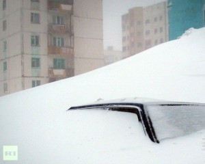 Car barely visible under a huge Russian snowbank