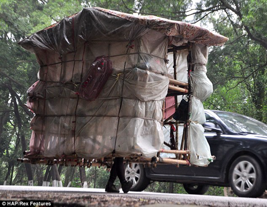 Chinese man carries his home around on his back like a snail
