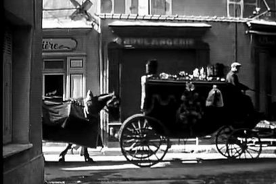 A funeral cortege for the village's victims passes in front of a local bakery