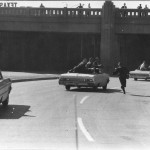 Photographer cars follow President limo as JFK is rushed to the hospital. One car slows to pick up a running photographer.