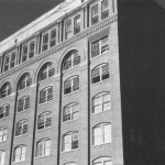 Powell photograph of Texas School Book Depository just seconds after the assassination. Bonnie Ray Williams visible in a fifth-floor window. Boxes that shielded Lee Harvey Oswald's Sniper's Nest visible on sixth floor.