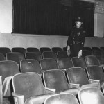 Dallas Police Officer inside the Texas Theater points to seat Oswald was found sitting in
