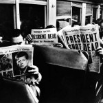 People of bus reading assassination newspaper headlines
