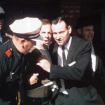 Lee Harvey Oswald being escorted from movie theater where he was captured