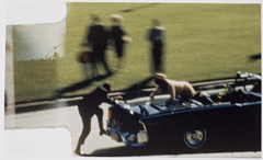 Secret Service agent quickly jumping on the presidential limo after Kennedy was shot