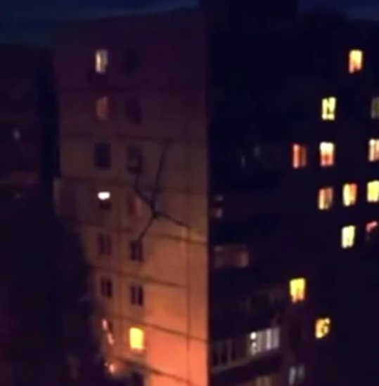 Slenderman - insect-like stick creature scaling side of Russian residential building