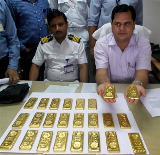 Airline officials show off the sold gold bars that were found in the bathroom of a Boeing 737.