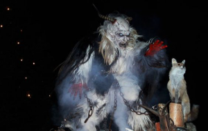 Krampus wearing chains reaching out to capture a small child