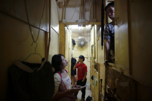 Stacked like lockers, a reporter interviews a resident of a coffin apartment
