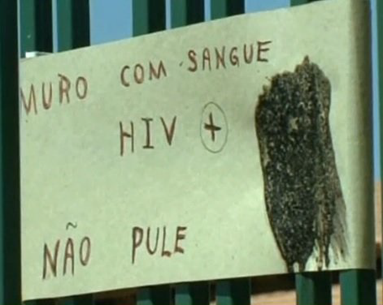 Sign informing potential burglars that the needles atop the fence contain HIV contaminated blood