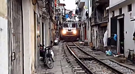 Crazy train in Old Quarter, Hanoi, Vietnam passes inches from front doors of residents' homes