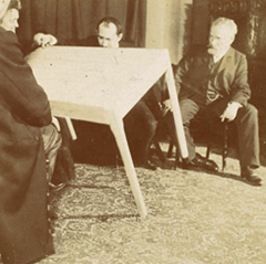 Researchers examine a table used in a seance