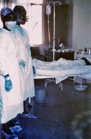 1976 photograph showing two nurses standing in front of Ebola case #3, who was treated, and later died at Ngaliema Hospital, in Kinshasa, Zaire