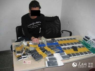 Police investigators show off the confiscated iPhones