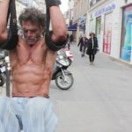 Homeless bodybuilder Sayagh Jacques does pullups using straps tied to street post