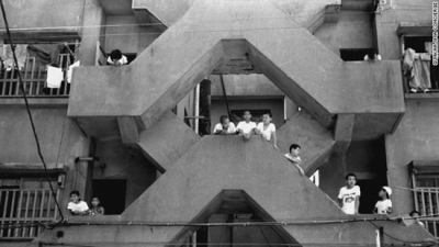 Children peer from the balcony of their Hashima apartment