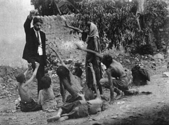 A Turkish official teases starving Armenian children with a piece of bread during the Armenian Genocide – 1915.