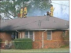 Firefighters on roof of burning house