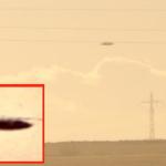 Metallic, disc-shaped UFO flying below powerlines above field in Bulgaria