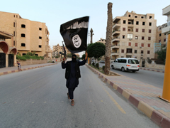 Islamic State (ISIS/Daesh) follower carrying gun and ISIS flag