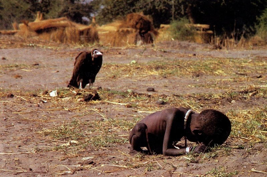 The Waiting for Death photo - starving Sudanse child awaits death while a vulture sits nearby