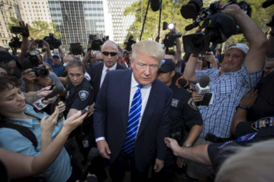 Donald J. Trump surrounded by reporters