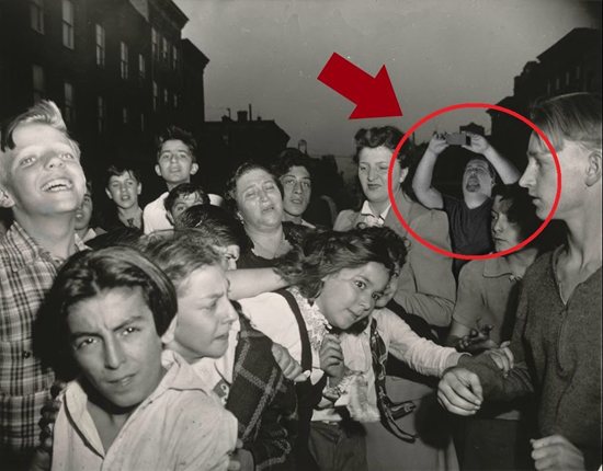 Man in old photo appears to be taking a picture with a modern-day cellphone thumb