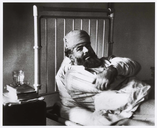 Ernest Hemingway in a hospital bed after one of his many accidents thumb