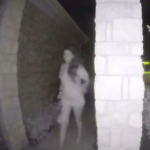 Surveillance video frame showing barefoot woman in broken restraints ringing home doorbell in middle of night