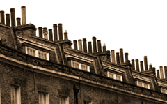 A dense cluster of chimneys atop a Victorian-era building